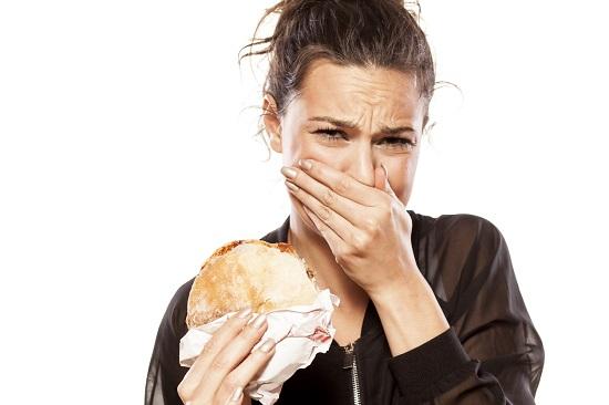 Femeie careia ii este scarba de sandvisul pe care-l mananca