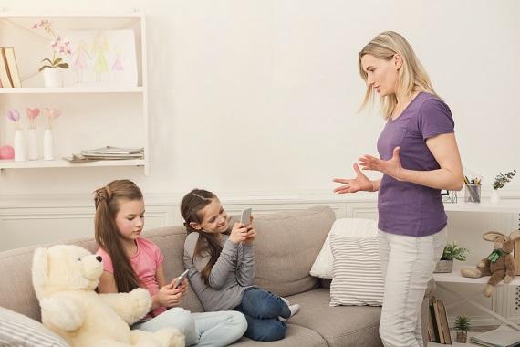 Mama ce incearca sa le vorbeasca fiicelor sale, antrenate in activitati cu telefonul mobil