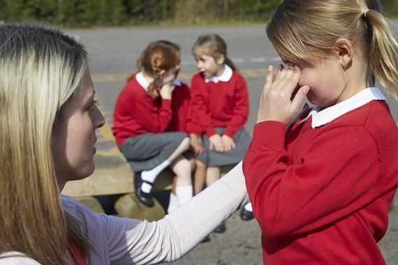Femeie ce consoleaza o fetita in curtea scolii
