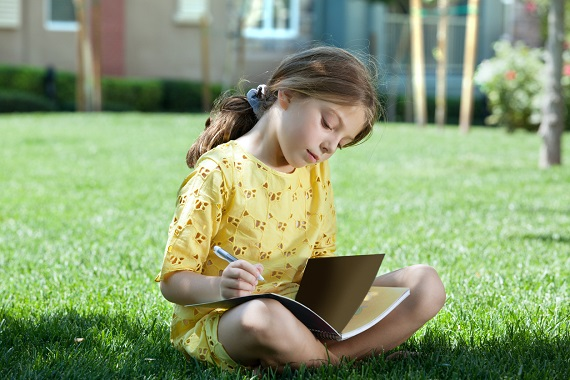 Fetita ce isi face temele in aer liber