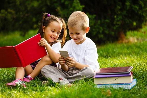 Fetita si baietel ce stau pe iarba