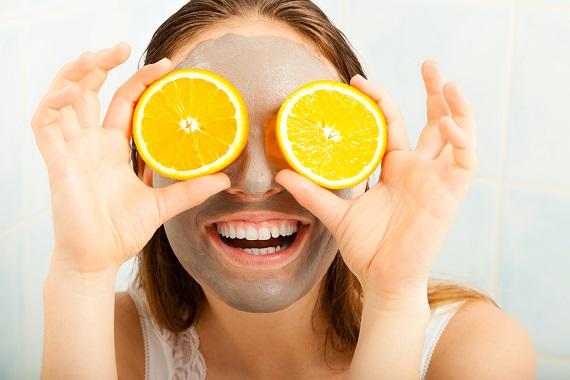 Femeie cu masca faciala si cu doua felii de portocala in dreptul ochilor
