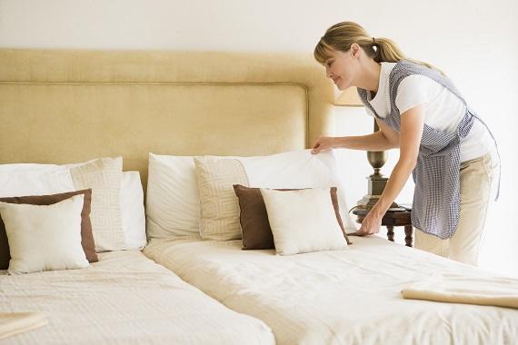 Femeie ce aranjeaza patul
