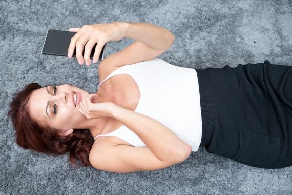 Femeie intinsa pe jos, tinand un smartphone in mana