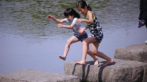 Fetite asiatice ce alearga pe malul unei ape