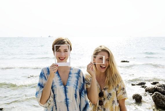 Doua femei vesele  la malul marii, ce vor sa isi faca poze