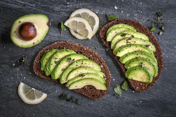 Sandvis cu avocado, pe paine graham, alaturi de avocado si felii de lamaie