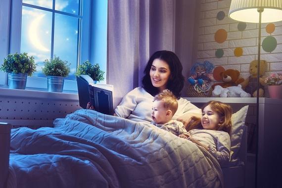 Mama care ii citeste fetitei inainte de culcare