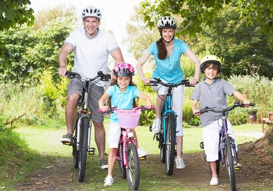 Familie ce se pregateste sa se plimbe cu bicicletele