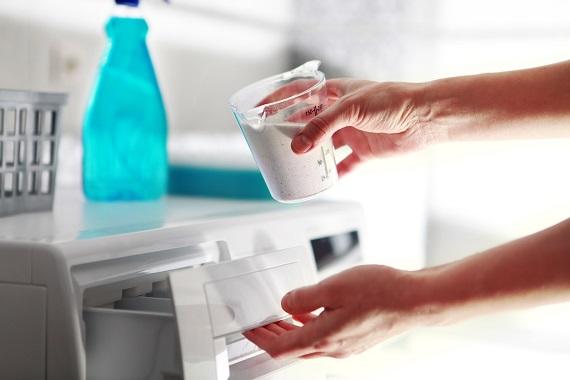 Femeie care pune detergent in masina de spalat