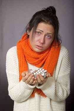 Fata care se simte rau si tine in mana blistere cu pastile