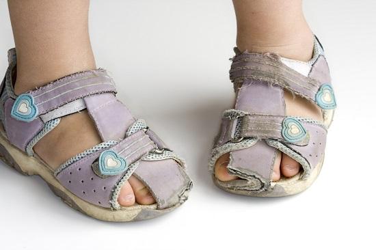 Copil incaltat in sandalute vechi