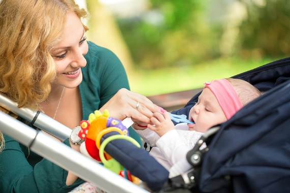 Mama ce ii pune la dispozitie bebelusului un inel pentru dentitie
