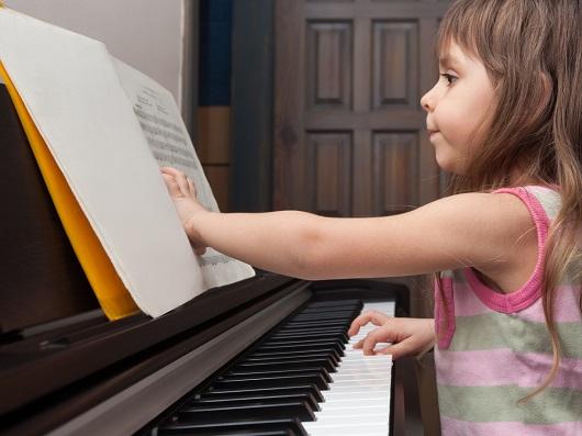 Fetita ce invata sa cante la pian
