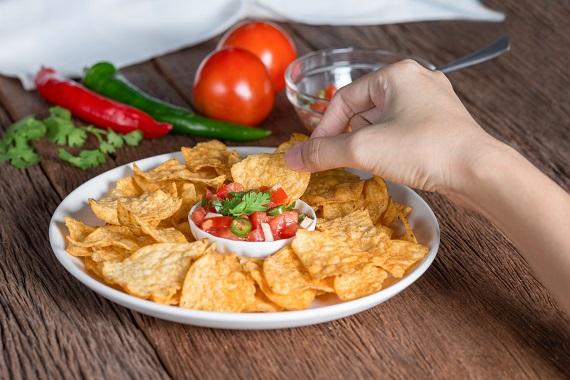 Femeie ce gusta din sos salsa cu nachos