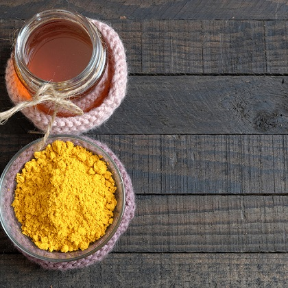 Borcan cu miere si recipient cu pudra de turmeric