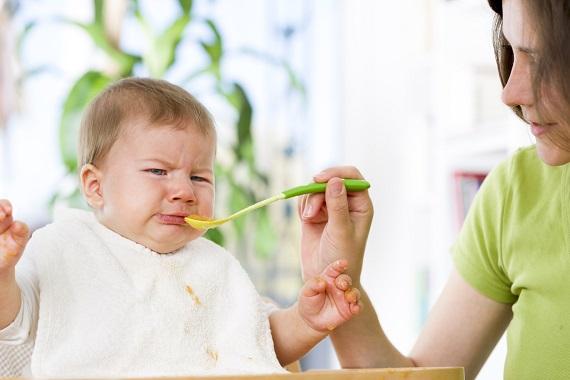 Bebelus ce plange in timp ce mama incearca sa-l hraneasca cu lingurita