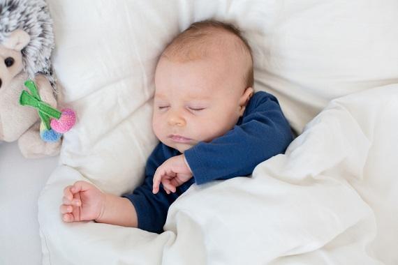 Bebelus ce doarme alaturi de jucarii