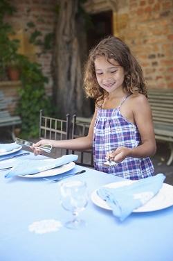 Fetita ce pune tacamuri pe masa