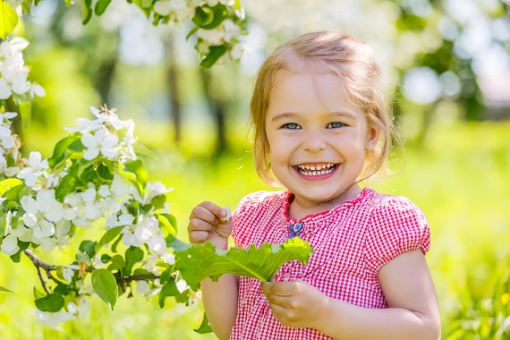 Fetita vesela, langa un copac inflorit