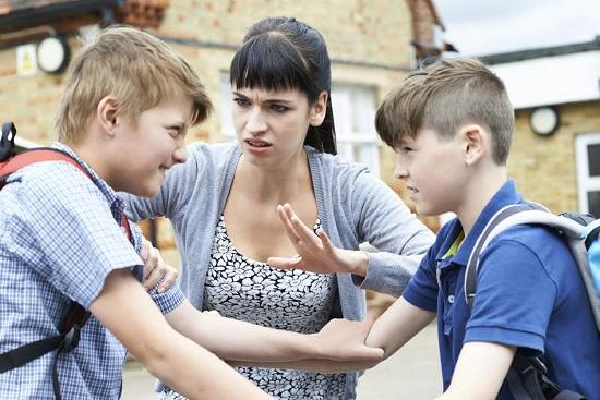 Femeie ce intervine in conflictul dintre doi baieti