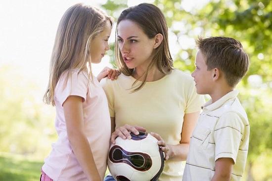 Mama cu doi copii, incercand sa discute cu fetita
