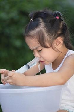 Fetita ce face spalaturi nazale cu o seringa