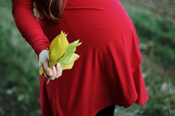 Femeie insarcinata ce tine in mana un manunchi de frunze