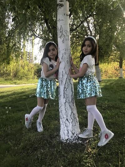 Fetite ce sunt fotografiate sub un copac si care poarta fustite stralucitoare si tenisi-ghetuta argintii