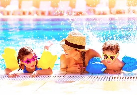Copii si mama ce stau in apa, sprijiniti de marginea piscinei