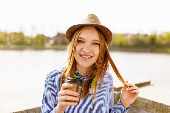 Fata binedispusa cu palarie, care tine in mana un pahar cu cafea
