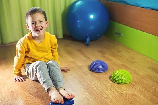 Baietel ce efectueaza niste exercitii speciale pentru picioare