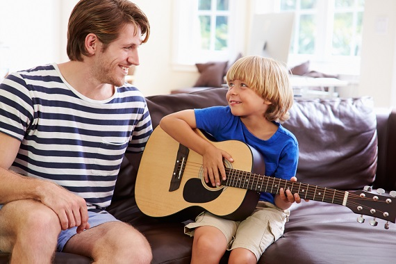 Tata ce este alaturi de fiul sau, care canta la chitara