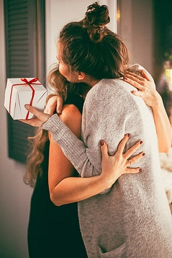 O fata a primit un dar si o imbratiseaza pe alta
