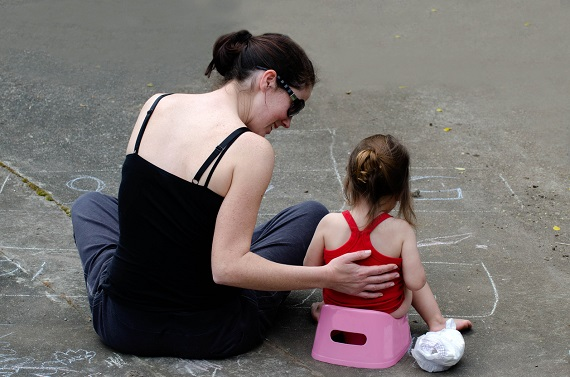 Mama ce sta langa fiica ei pe strada, in timp ce micuta este pe olita