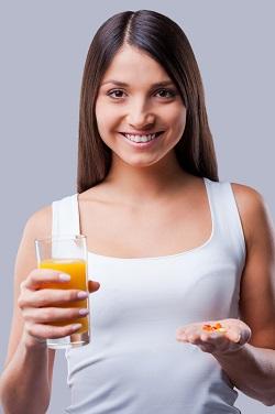 Femeie ce are intr-o mana un pahar cu suc si in cealalta niste pastile