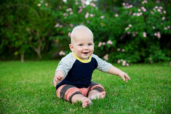 Bebelus ce sta pe iarba