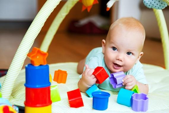 Bebelus ce se joaca pe burtica