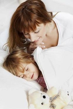 Mama se uita la copilul ei, care doarme