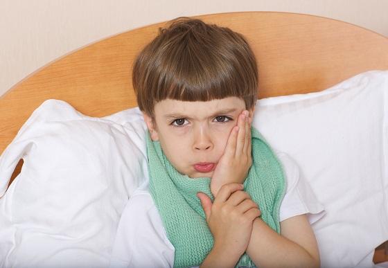 Copil cu durere de masea, ce sta in pat