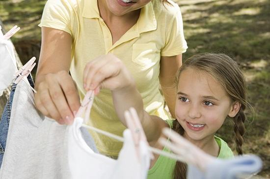Fetita intinde rufele cu mama