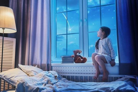 Fetita se uita la stele, de la geamul din camera ei