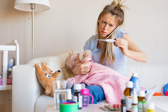 Fetita bolnava, cu febra si mama care telefoneaza dupa ajutor