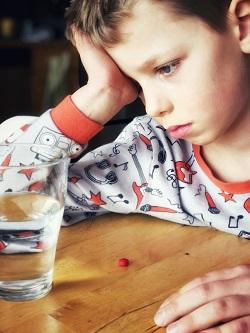 Copil deprimat, ce are o pastila si un pahar cu apa langa el