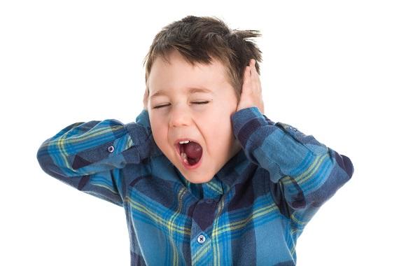 Copil ce isi duce mainile la urechi si tipa