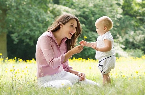 Mama ce ii ofera copilului ei o papadie