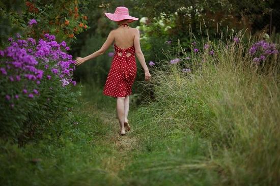 Fata cu palarie, ce merge desculta printre flori