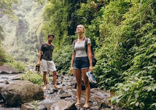 Cuplu mergand pe jos in natura, incercand sa treaca un parau