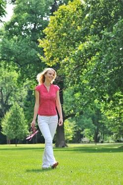 Tanara ce merge desculta prin parc