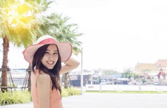 Fata asiatica, ce poarta o palarie de soare in nuante de roz
